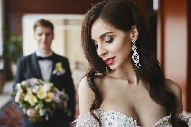 Belle et plantureuse brune modèle fille avec un maquillage lumineux et un corps sexy dans une robe longue à la mode avec un décolleté séduisant et des boucles d'oreilles de luxe avec des diamants souriant et posant à l'intérieur