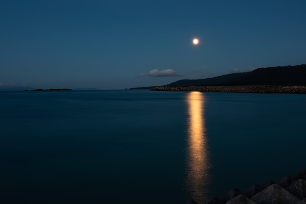 Belle pleine lune se levant derrière la montagne se reflétant dans la mer au crépuscule. l'île d'iriomote.