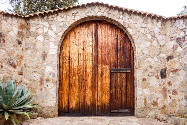 Belle porte en bois avec une partie haute ronde, dans un mur en pierre d'une propriété rurale.