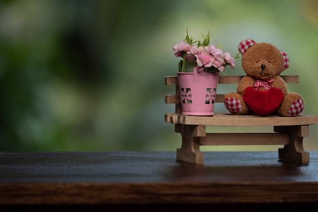 Belle poupée ours avec des fleurs dans un vase posé sur le banc en bois.