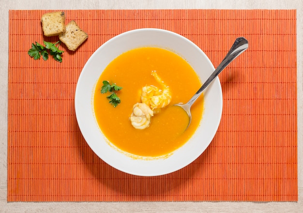 Belle présentation de la soupe de poisson dans une assiette blanche sur fond orange.