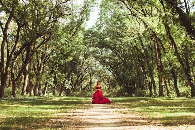 Belle princesse avec couronne en robe rouge nuageuse debout sur le chemin dans la forêt de conte de fées.