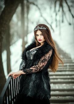 Belle reine sombre. princesse gothique avec une couronne dans une longue robe sombre.