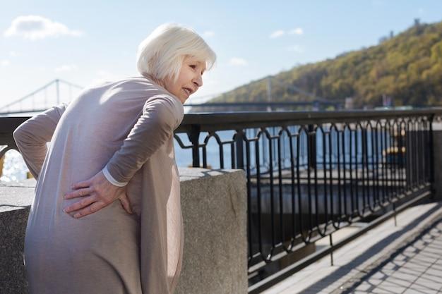 Belle retraité perplexe aux cheveux blancs debout et mettant la main sur son dos en marchant près de la rivière
