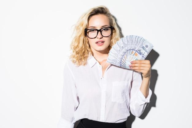 Belle réussite jolie femme d'affaires détenant des billets d'un dollar, isolé sur un mur blanc