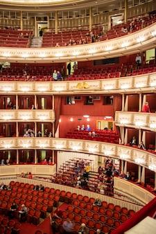 Belle et riche décoration de l'intérieur de l'auditorium de l'opéra national de vienne avec parterre et balcons et personnes avant de commencer la représentation à vienne, en autriche.