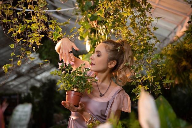 Belle rose. agréable jolie femme tenant un pot de fleur tout en touchant une fleur tendre