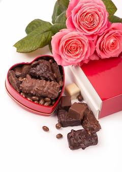 Belle rose et chocolat noir pour la saint-valentin sur fond blanc isolat.