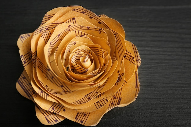 Belle rose faite de notes de musique sur table en bois libre