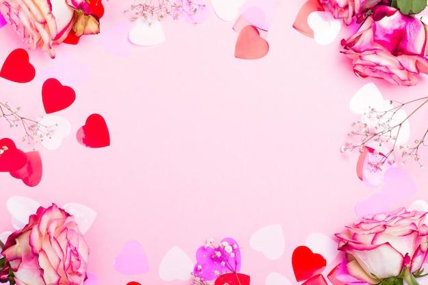 Belle rose rose, coeurs de confettis décoratifs et ruban rose sur fond rose saint valentin