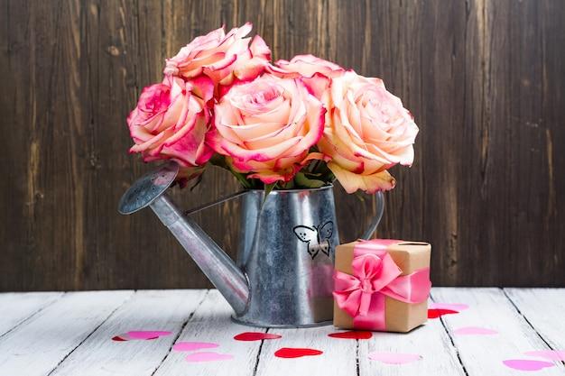 Belle rose rose dans un bidon d'arrosage sur fond en bois