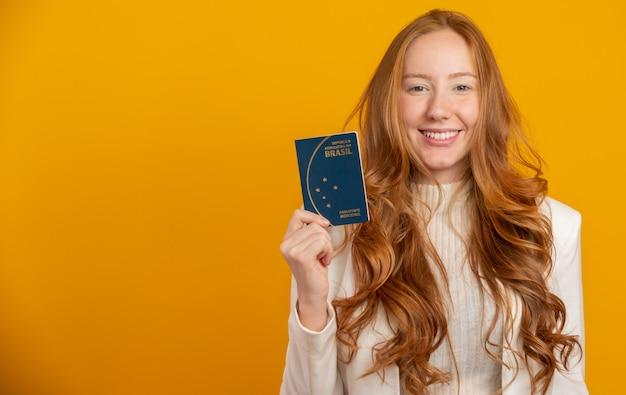 Belle rousse aux cheveux bouclés en voyage. prochain voyage. fille tenant un passeport brésilien. sur jaune.