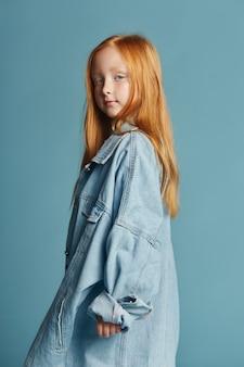 Belle rousse aux cheveux longs dans une grande veste en jean longue bleue