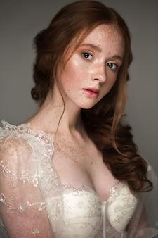 Belle rousse avec des cheveux parfaitement bouclés et un maquillage classique