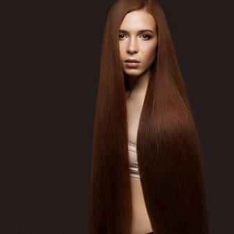 Belle rousse avec des cheveux parfaitement lisses et un maquillage classique. beau visage.