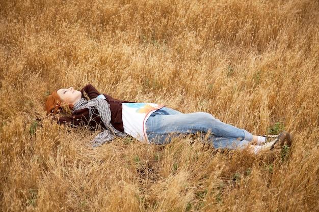Belle rousse couchée sur l'herbe jaune. temps de saison d'automne