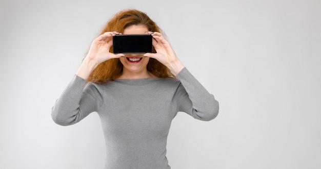 Belle rousse heureuse souriante jeune femme en vêtements gris tenant un téléphone portable devant son visage