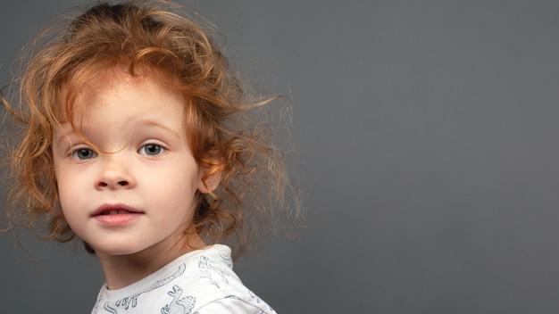Belle rousse petite fille sur fond gris avec espace de copie, bébé mignon maquette sur bannière.