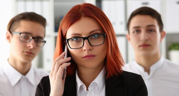 Belle rousse souriante femme d'affaires parler téléphone portable en portrait de bureau