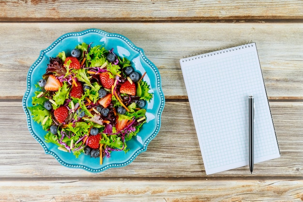Belle salade avec bloc-notes et stylo pour mémo rapide