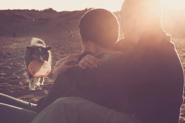 Belle scène avec un couple caucasien homme et femme étreints avec amour à la plage et un joli chien border collie allant vers eux avec un jeu demandant de jouer ensemble pour toujours pendant les loisirs en famille