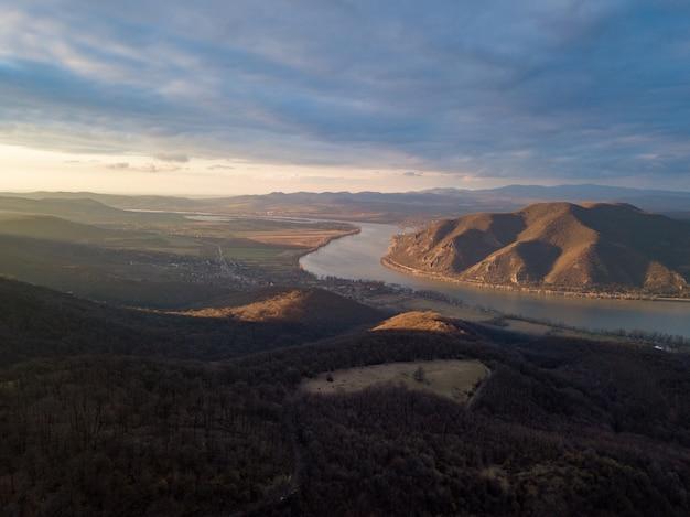 Belle scène d'une rivière entre collines et forêt sous le ciel nuageux