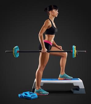 Belle séance d'entraînement de femme de forme physique avec la barre