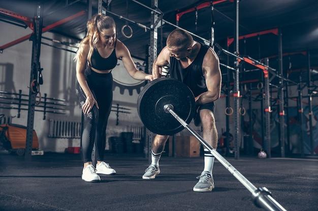Belle séance d'entraînement de formation de jeune couple sportif dans la salle de sport ensemble