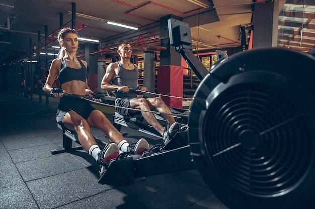 Belle séance d'entraînement de jeune couple sportif dans la salle de gym ensemble. homme de race blanche s'entraînant avec une formatrice.