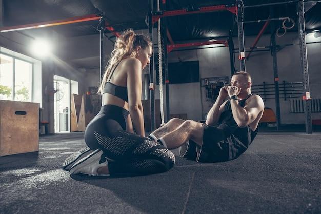 Belle séance d'entraînement de jeune couple sportif dans la salle de gym ensemble.