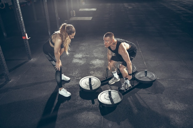 Belle séance d'entraînement de jeune couple sportif dans la salle de gym ensemble