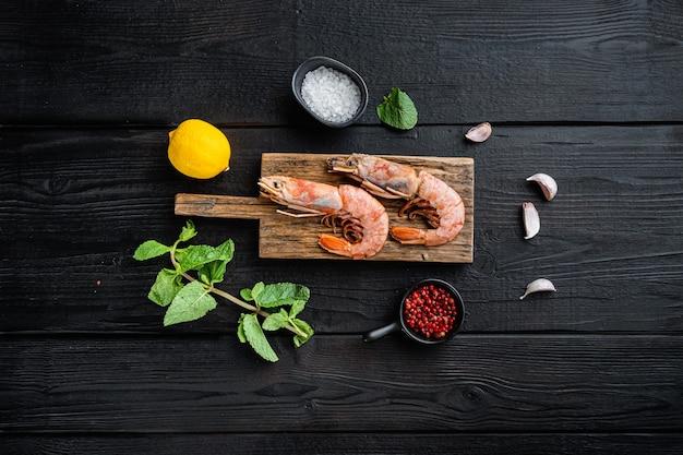 Belle sélection de crevettes tigrées sur planche de bois sur table en bois noir, vue de dessus, photo alimentaire.