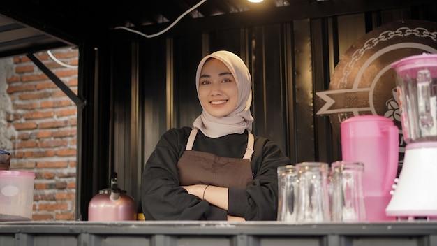 Belle serveuse asiatique avec des bras a l'air cool en gardant le conteneur de stand de café