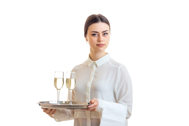 Belle serveuse avec champagne sur un trey en regardant la caméra isolée sur fond blanc