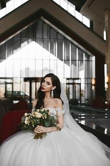 Belle et sexy modèle femme, avec un corps parfait et de gros seins, dans la robe de mariée à la mode détient un élégant bouquet de fleurs fraîches et posant dans un intérieur moderne de luxe