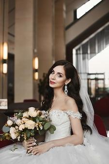 Belle et sexy modèle femme dans la robe de mariée à la mode tient un bouquet de fleurs fraîches