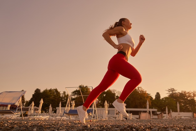 Belle silhouette de femme sportive en jogging sportswear à l'aube du matin