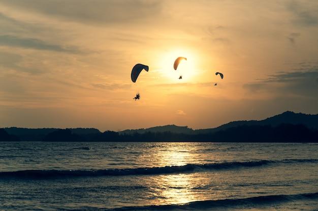 Belle silhouette de parapente volant dans le ciel du coucher de soleil sur la plage.