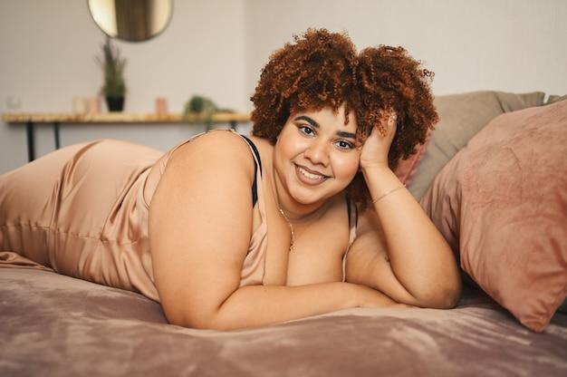 Belle sinueuse grande taille femme noire africaine cheveux afro allongé sur le lit en robe rose poudré en soie confortable