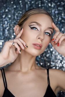 Belle soirée maquillage des yeux d'une femme blonde sur un fond brillant. portrait en gros plan d'une femme, maquillage parfait des yeux, soins de la peau