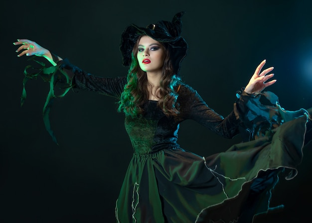 Belle sorcière avec un chapeau fait le sabbat des sorcières de la fête d'halloween