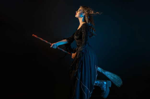 Une belle sorcière sur un manche à balai vole vers le sabbat