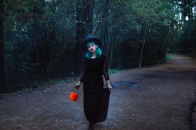 Belle sorcière marchant le long du sentier forestier