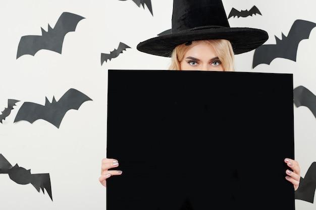 Belle sorcière se cachant derrière le tableau noir