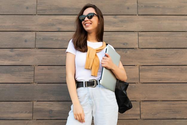 Belle souriante heureuse charmante jeune femme brune regardant de côté tenant un ordinateur portable et