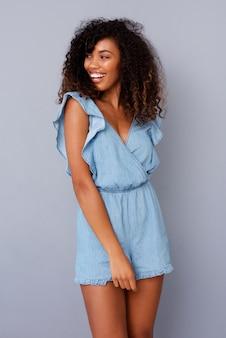 Belle souriante jeune femme noire contre le mur gris