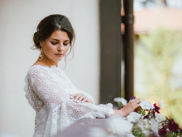 Belle souriante mariée jeune femme brune en robe de dentelle blanche sur le balcon,