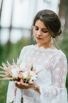 Belle souriante mariée jeune femme brune en robe de dentelle blanche avec bouquet de mariage boho