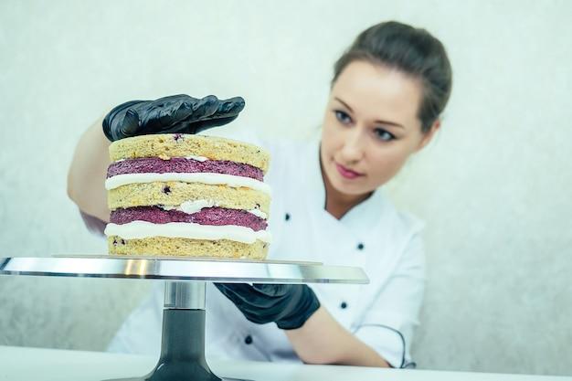 Une belle et souriante pâtissière portant des gants noirs et un uniforme de travail blanc prépare un gâteau dans la cuisine. confiseur, gâteau, cuisine.