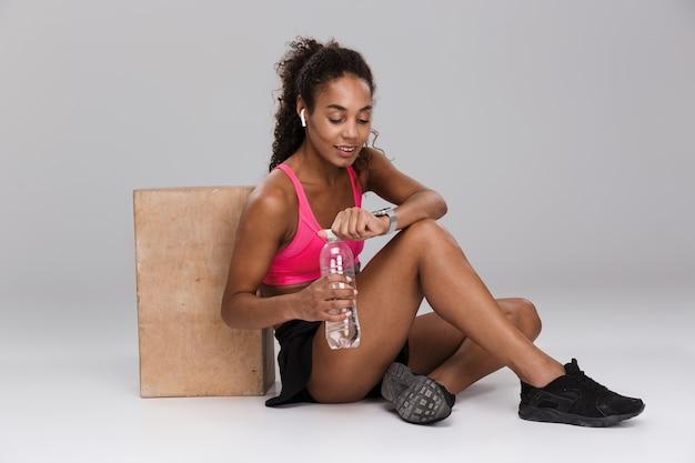 Belle sportive afro-américaine dans les écouteurs au repos tout en étant assis et boire de l'eau à partir d'une bouteille isolée sur fond gris